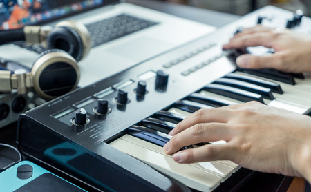 Musician is recording Keyboard on to Computer Music Studio Stock Photo