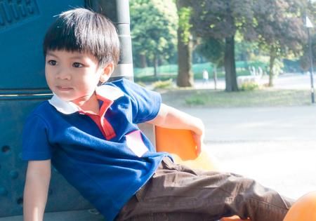 Asian boy sitting in playground playhouse