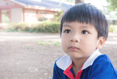 Sad Asian boy portrait in the park Stock Photo