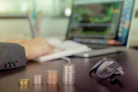 ビジネスの男性はコイン スタック成長株式取引について分析します。 写真素材