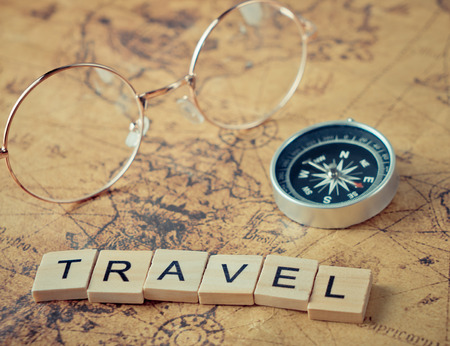 Travel text with vintage compass and glasses on map Stock Photo