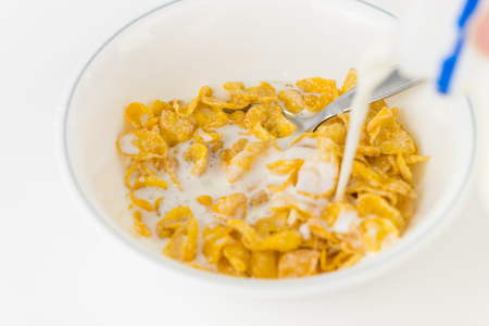 Pouring milk onto a bowl of sweetened cereal Stock Photo