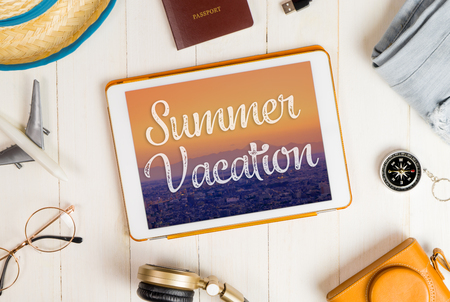 Summer Vacation on tablet with travel accessories