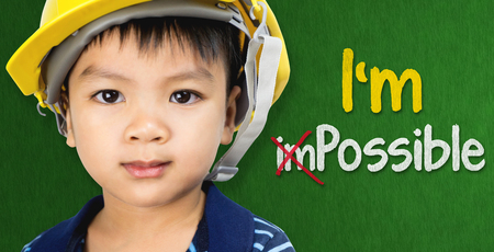Boy wearing engineering hat with Im possible text for Educational and occupation possibility concept Stock Photo