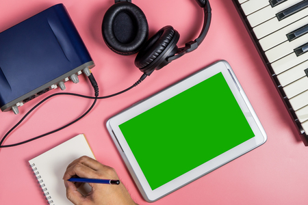 earbud: Songwriter musician is using tablet for Music producing.