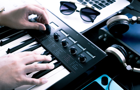 Music producer is producing Music on synthesizer keyboard Stock Photo - 80678766