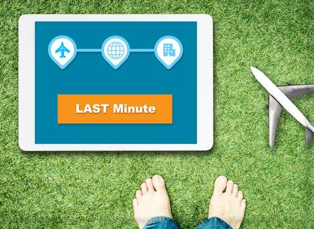 Last minute boeking op tablet-scherm met grassen en op blote voeten voor Relax vakantie concept