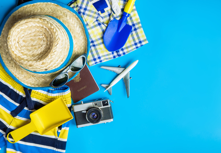 Boy travel accessories, fashion  and toys on blue copy space