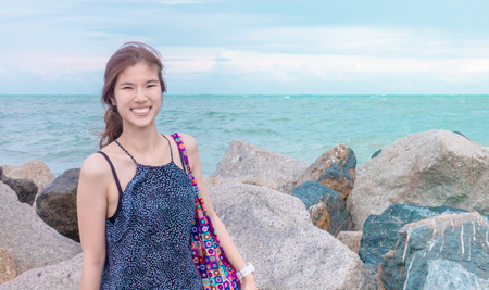 Happy Asian girl with rock cliff ocean background