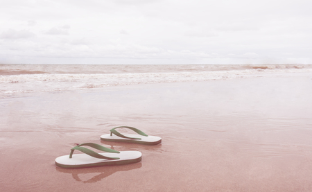 Beach Sandals Flipflip on sandy beach in vintage tone 版權商用圖片