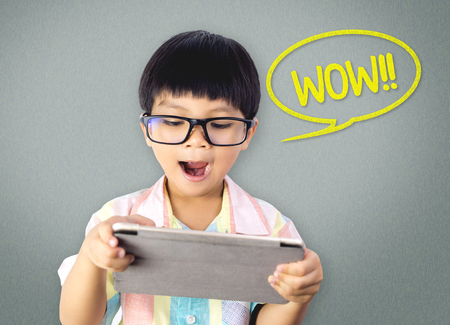 Asian nerdy boy is exciting with what on the Tablet Imagens
