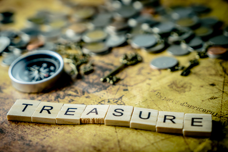 Vintage treasure hunting concept with coins and compass Archivio Fotografico