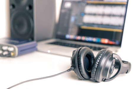 Black studio headphone in DAW music studio laptop