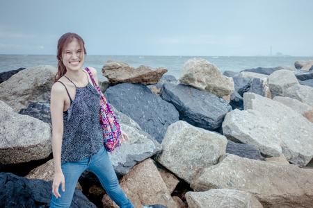 Asian lady standing on rock sea shore Фото со стока - 82869671
