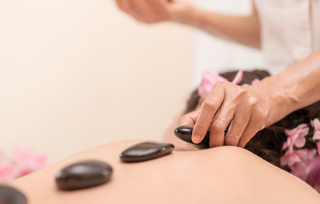 Spa Therapist is placing hot stone on to women back Banco de Imagens - 82354007