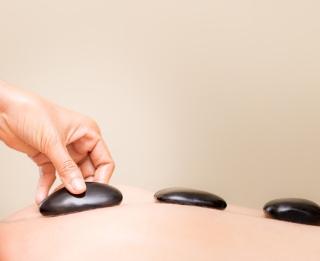 Hand is placing black hot stone on a women back Stock Photo