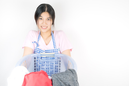 Funny Housewife is carrying a basket full of laundry clothes. Stock Photo