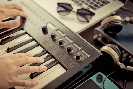 Musician is recording keyboard on to Computer Music studio