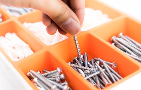 Hand nimmt einen Schraubennagel aus der orangefarbenen Werkzeugkiste Standard-Bild - 83690607