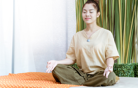 Young Thai girl is meditating before taking spa course Stock Photo