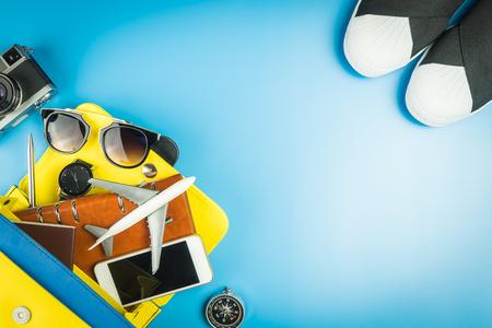 Women handbag full of travel objects on blue background