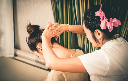 head and  back: Thai Massage Therapist is massaging a women neck Stock Photo