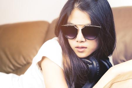 Aziatische Vrouwen met zonnebril die op een bank liggen