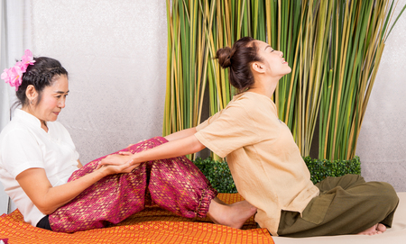 Women is getting her arm stretched by Thai Massage therapist