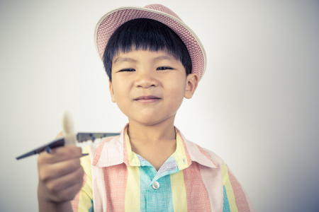 Boy traveler holding a toy plane for world travel concept Stock Photo