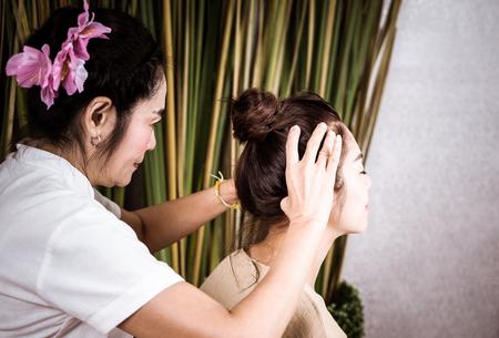 Thai Massage Therapist is giving head massaging