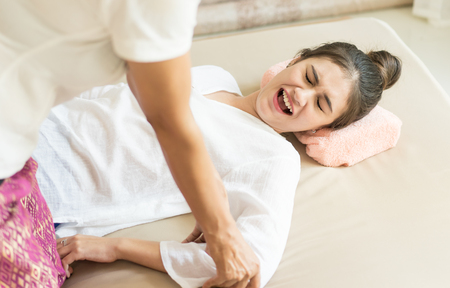 Women is hurting while Therapist is pushing her arm for reflexology in Thai massage course