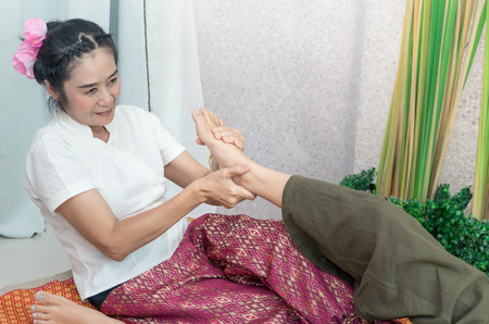 Therpist is giving a Thai foot massage in a spa