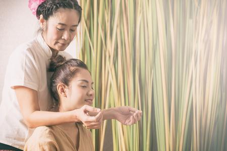 Women is getting shoulder massage from Thai therapist