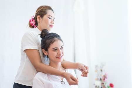 Women is getting shoulder massage by Thai Therapist Stock Photo