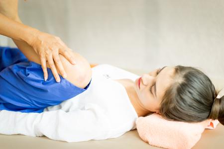 Thai Massage Therapist is Bending a women leg up high.