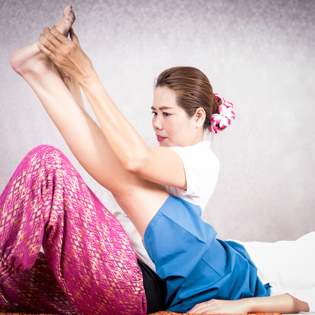 Thai Massage Therapist is stretching a women leg up high.