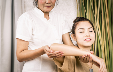 Women is getting Thai massage stretching position on her arm.