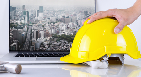 construction project: Civil Engineer is picking up safety helmet with tokyo background Stock Photo