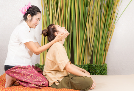 タイのスパのマッサージの療法士は女性の首を伸ばしてください。 写真素材