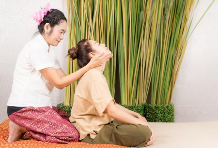 태국 스파 마사지 치료사는 여성 목을 스트레칭하고 있습니다. 스톡 콘텐츠