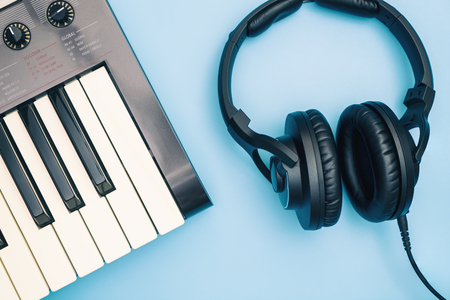 Music keyboard and Music headphone on blue background Stock Photo