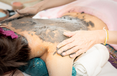 Women is getting Clay scrub on the back in Spa