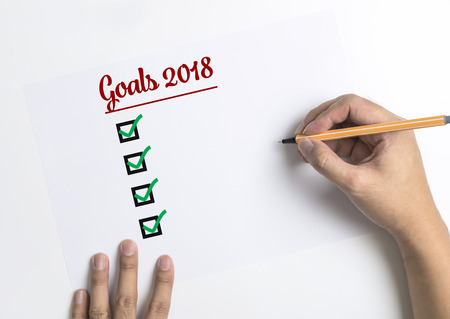 Hand writing down checklists for 2018 Goals on paper top view copy space Stockfoto