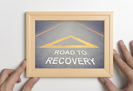 Hand holding wooden frame with road to recovery direction concept