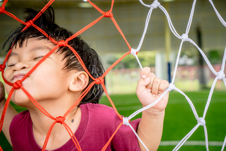 net: Boy playing with Soccer Football Goal net for sport concept