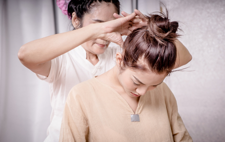 Therapist is using finger to massage women neck in Thai Massage spa