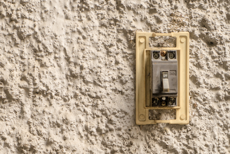 Electrical breaking switch on stucco wall copy space