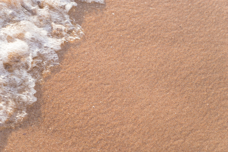 Wet beach sand with wave motion blur