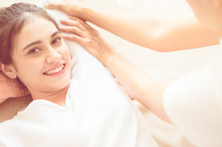 Happy woman is receiving massage treatment in Thai Spa Stock Photo