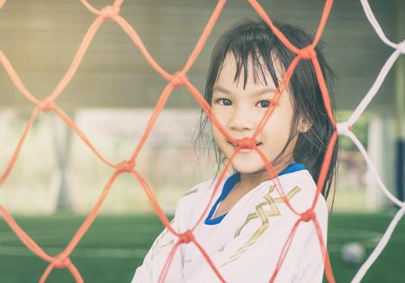 Happy Girl behind Soccer Football goal net for children sport concept Stock Photo
